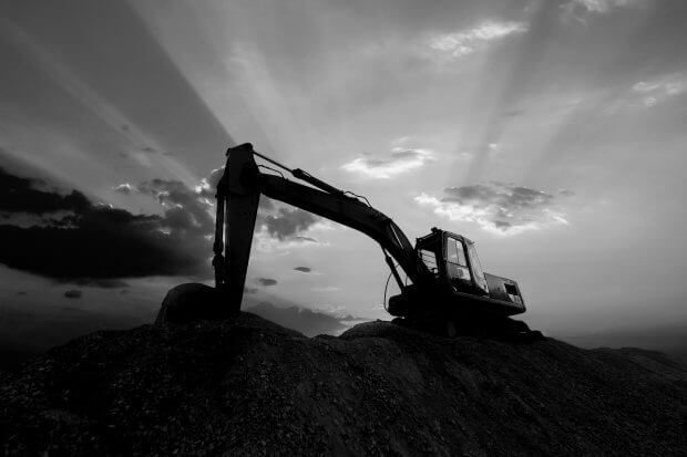 Silhouette excavator working on construction site.