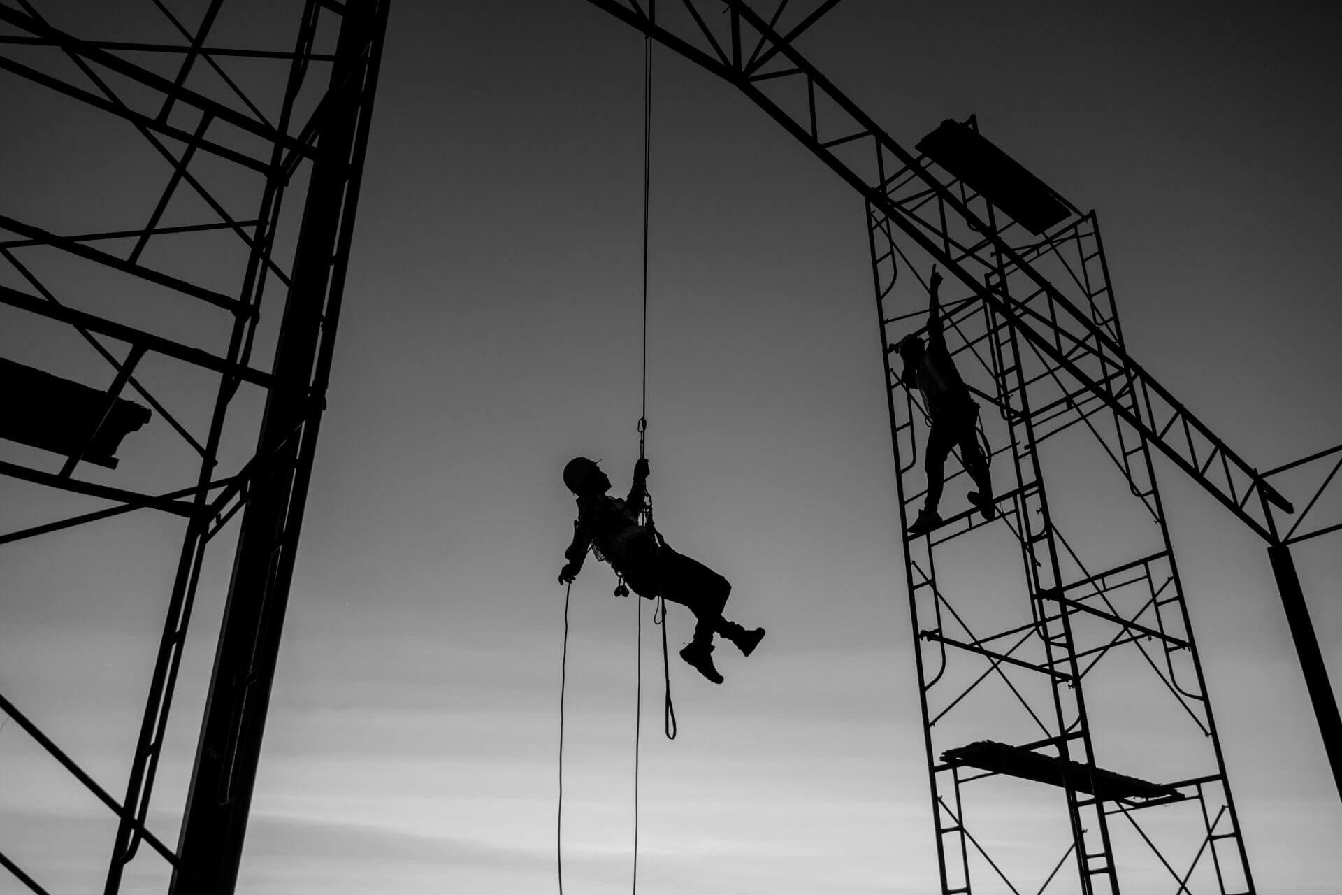 Male working abseiling on a construction site silhouette workerloading=