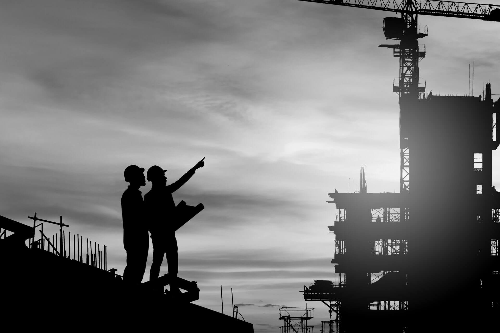 Silhouette of Engineer and worker checking project at buildingloading=